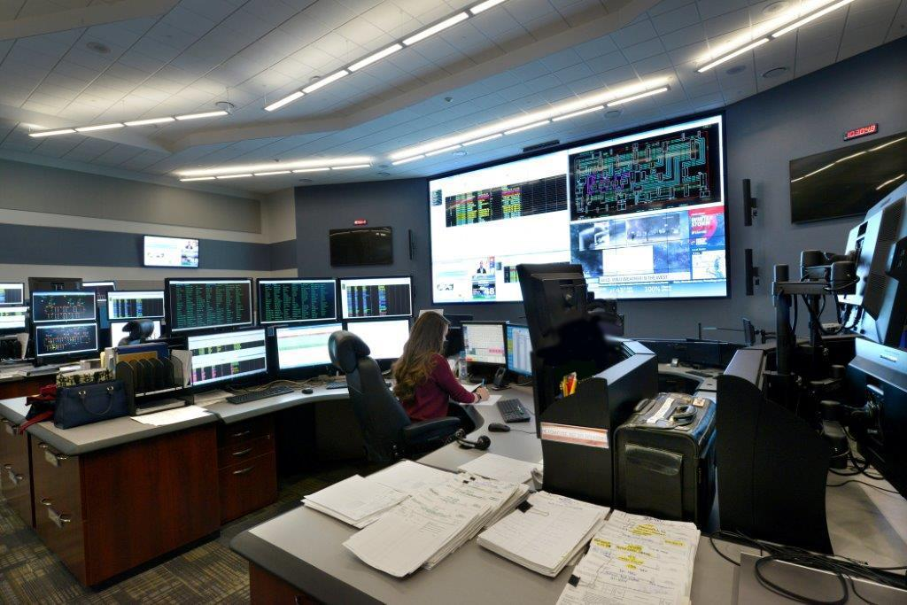 Electric utility control room with console workstations and large video display wall